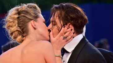 "US actress Amber Heard kisses her husband US actor Johnny Depp as they arrive for the screening of the movie ""The Danish Girl"" presented in competition at the 72nd Venice International Film Festival on September 5, 2015 at Venice Lido.  AFP PHOTO / GIUSEPPE CACACE"