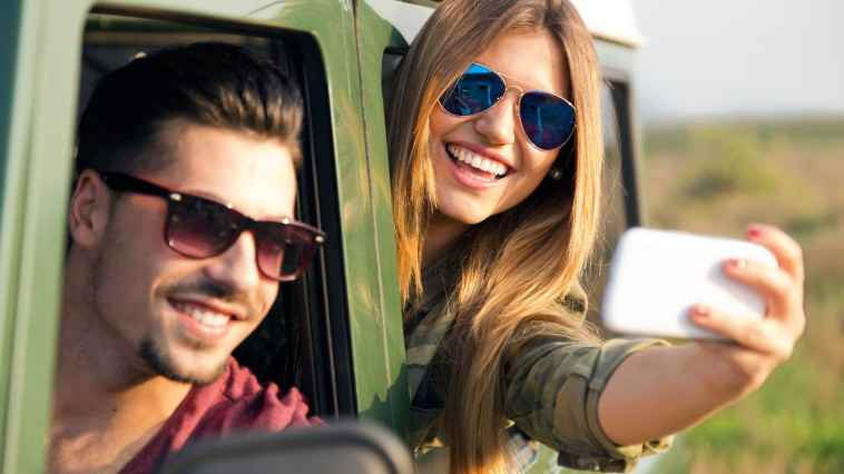 Outdoor portrait of pretty couple taking selfie with smartphone in the car.