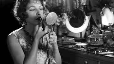 circa 1919: Norma Talmadge (1893 - 1957), the American silent screen heroine who was contracted to United Artists, applying lipstick with particular care at her dressing table at the studio.